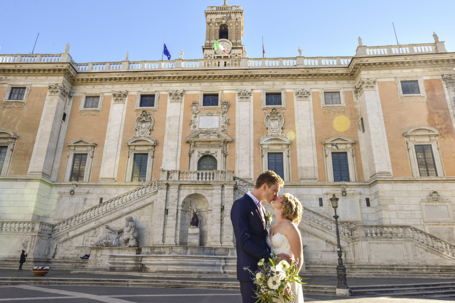 Bridal couple kissing in front of Campidoglio Palace