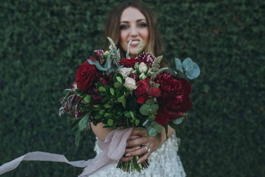 Bridal bouquet in deep red and dark green tones