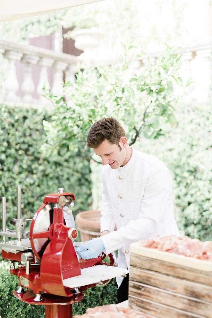 Italian waiter preparing prosciutto